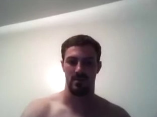 Handsome male is jerking in the guest room and shooting himself on computer webcam