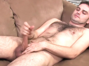 Hairy stud lays on the couch and starts playing with his hard pole