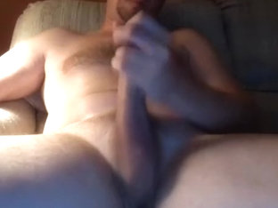 Handsome guy is masturbating in the guest room and shooting himself on computer webcam