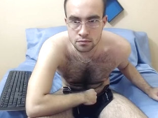 Enchanting guy is playing in the bedroom and memorializing himself on computer webcam