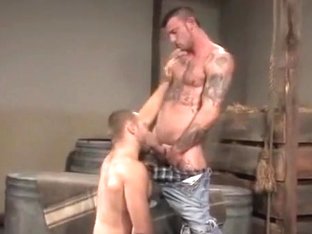 Tattooed gay studs in a barn