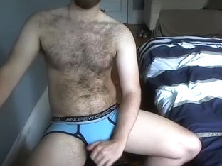 Pretty guy is relaxing in the apartment and filming himself on computer webcam