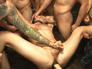 Horny party goers gangbang and fist a bound stud's ass