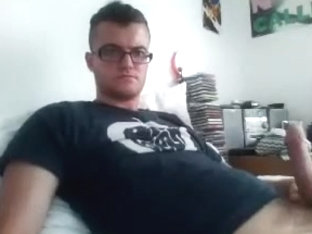 Handsome male is relaxing in a small room and memorializing himself on computer webcam