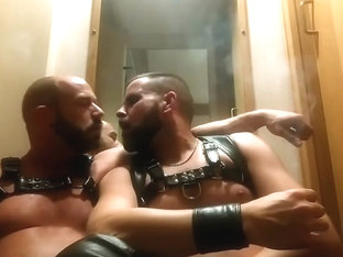 Leather muscled hunks smoking together