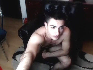 Handsome male is frigging in a small room and filming himself on webcam