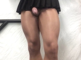 Tan thighs, cock in  black mini skirt .