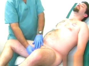 Young beer-bellied stud examined by doctor
